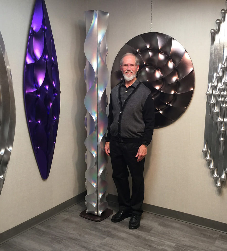 Thomas Newhouse standing with his sculptures